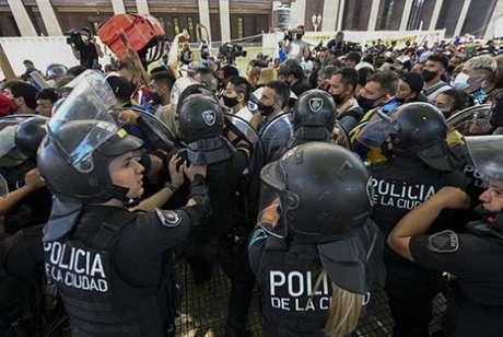 Policiais tentam dispersar os torcedores (Foto: JUAN MABROMATA / AFP)