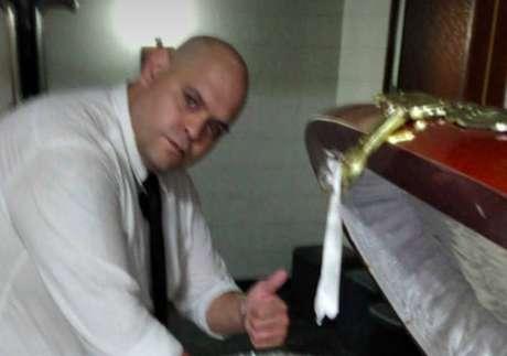 Funcionário da funerária ao lado de caixão de Maradona.
