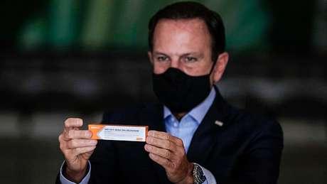 O governador de São Paulo, João Doria, apresenta a embalagem da CoronaVac, desenvolvida pelo laboratório chinês Sinovac e testada no Brasil pelo Instituto Butantan. A taxa de eficácia dessa candidata ainda não é conhecida