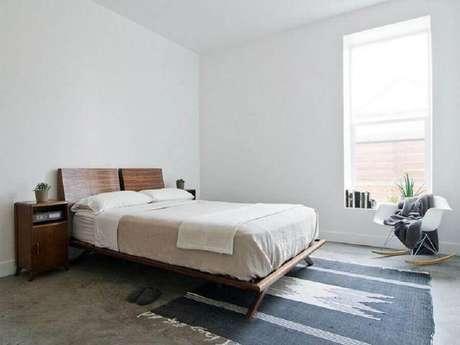 41. Quarto de casal minimalista decorado com tapete escandinavo e cama de madeira – Foto: Lucy Call