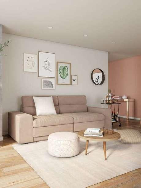 27. Sala com sofá bege decorada com puff branco e mesa de centro redonda de madeira – Foto: Pinterest