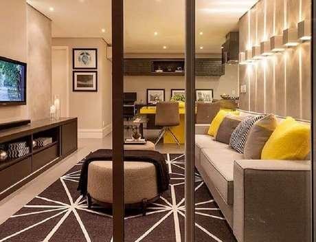 28. Decoração moderna para sala bege e amarela com arandelas na parede – Foto: Trico Decor