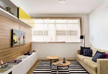 32. Tapete listrado e painel de madeira para decoração de sala com sofá bege simples – Foto: Jeito de Casa