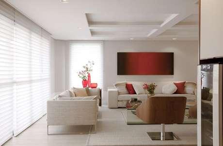 39. Os detalhes em vermelho deixam a decoração da sala bege mais cheia de vida – Foto: Marcelo Rosset