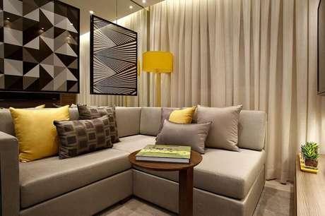 42. Sala bege pequena decorada com detalhes em amarelo e quadros modernos – Foto: Marel