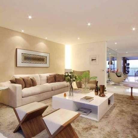 46. Sala de estar bege decorada com tapete felpudo, mesa de centro branca e puffs de madeira – Foto: Pinterest