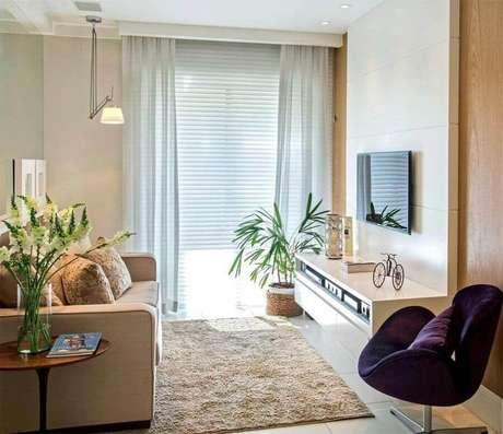 49. Sala bege pequena decorada com luminária articulável de teto e poltrona roxa – Foto: Muito Chique