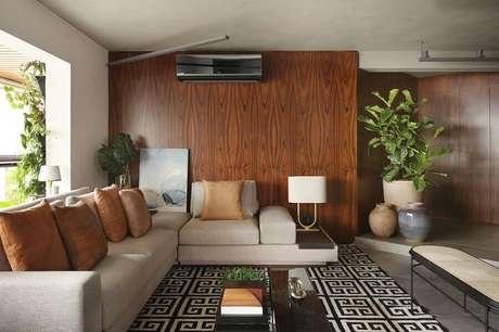 51. Parede de madeira e almofadas marrons para decoração de sala com sofá bege e tapetes geométricos – Foto: Quattrino Arquitetura