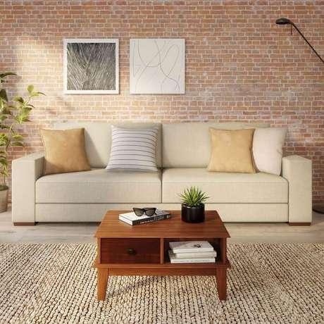 5. Sala com sofá bege decorada com parede de tijolinho – Foto: Pinterest