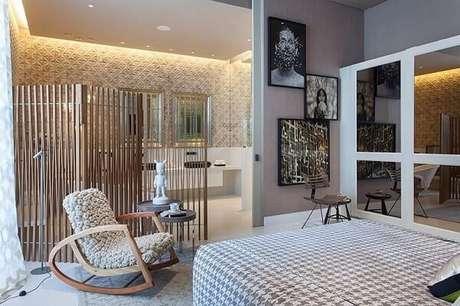 51. Cadeira de pelinho branco e banco de madeira decoram o quarto com suíte. Projeto por Denise Barretto