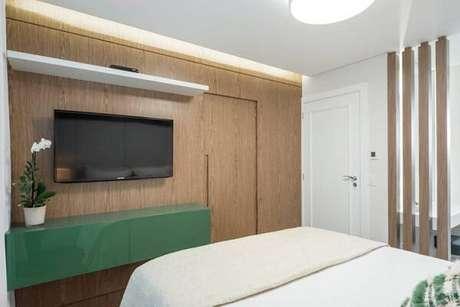 9. Modelo de quarto com suíte onde a porta do banheiro segue a mesma marcenaria do painel de TV. Fonte: Pinterest