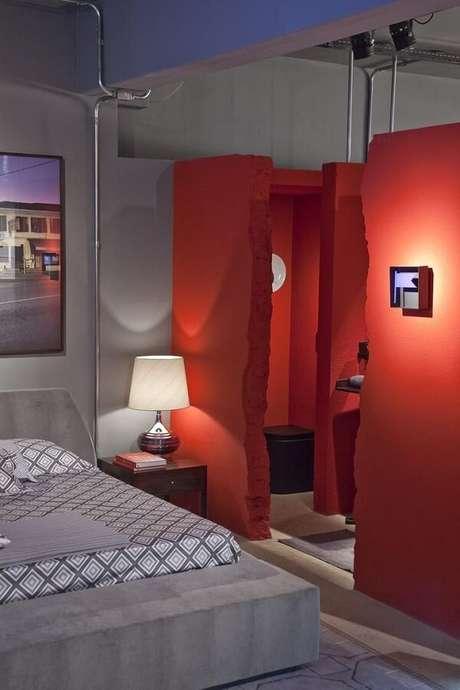 39. Paredes sem porta e em tom vermelho se destacam nesse projeto de quarto com suíte. Projeto por Antônio Ferreira Junior e Mário Celso Bernardes