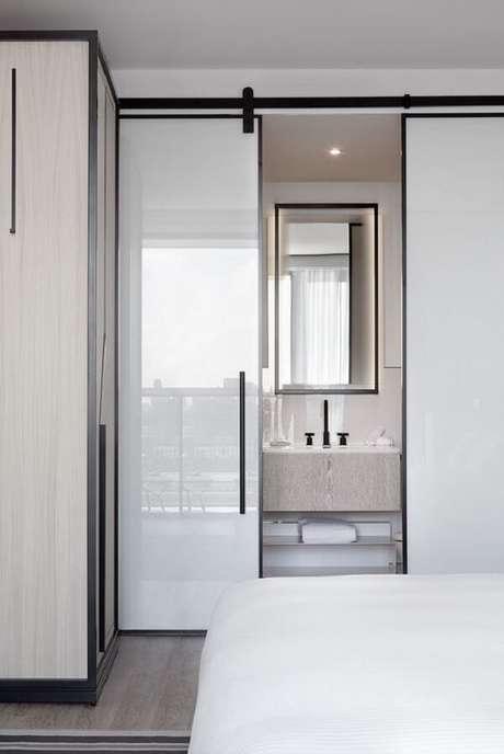 27. Porta de correr branca para quarto com suíte pequeno. Fonte: Studio Munge