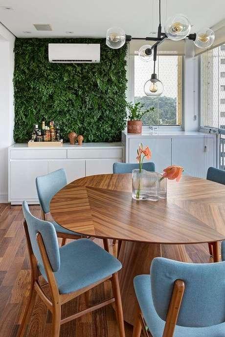 1. Mesa para varanda gourmet com cadeiras azuis e jardim vertical – Via: Apartamento 203