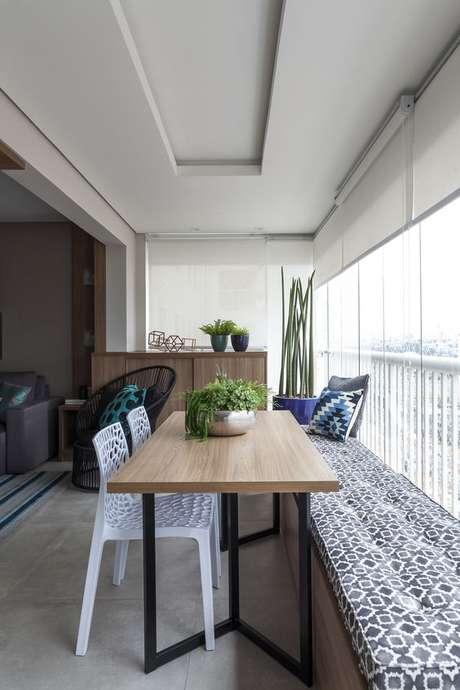 47. Mesa para varanda gourmet de madeira com bancos para ganhar espaço – Via: Rubiam Vieira Interiores