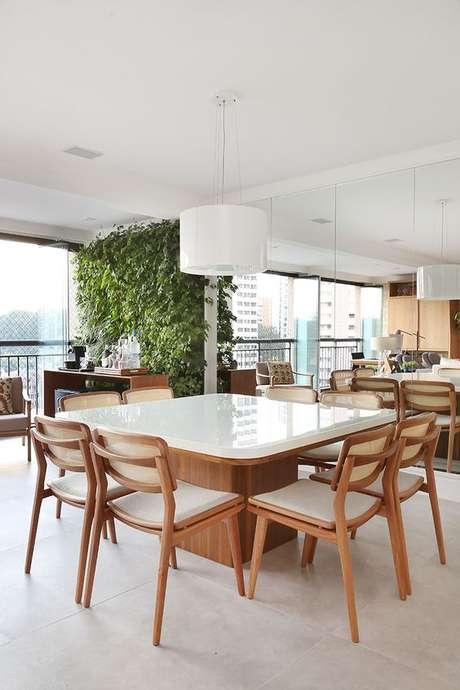 75. Mesa de madeira para varanda gourmet ampla com jardim vertical na decoração – Via: Casa de Valentina