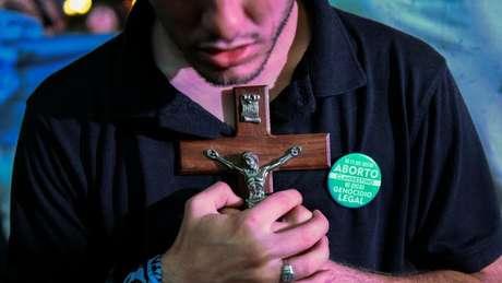 Manifestante contra legalização do aborto segura crucifixo em protesto em frente ao Congresso