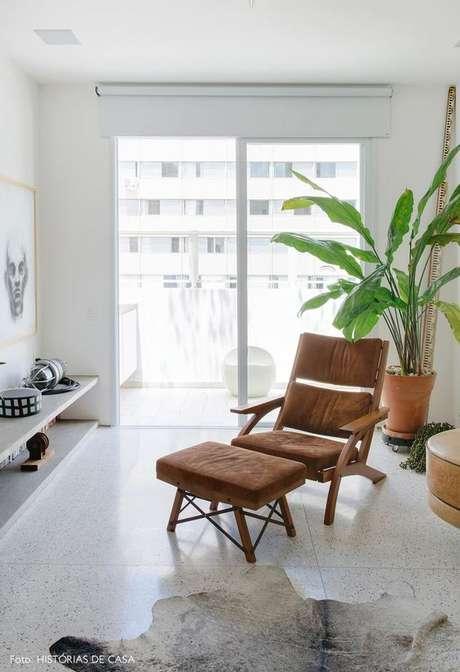 41. Poltrona com puff marrom na sala de estar aconchegante – Via: Histórias de Casa