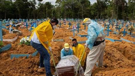 Homens enterram caixão em cemitério no Manaus