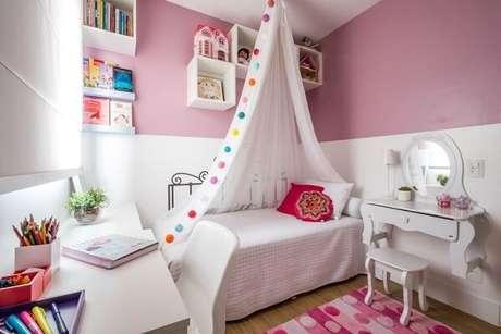 46. Móveis e prateleira para quarto infantil de livros branco se contrastam com a parede rosa. Fonte: SP Estudio