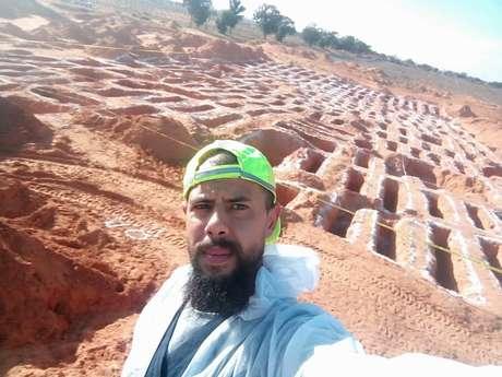 Wadah al-Keesh ao lado de algumas das covas que ajudou a escavar