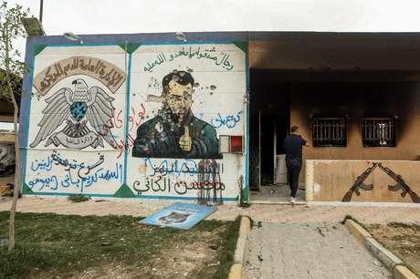 """Um mural desfigurado de Mohsen, o """"ministro da defesa"""", no centro de detenção dos irmãos"""