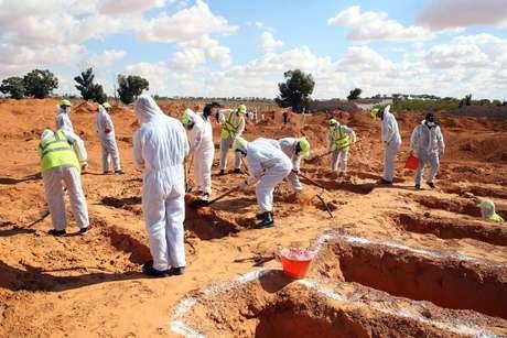 Homens em trajes de proteção brancos desenterrando corpos de mortos