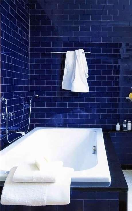 32. Banheiro com revestimento azul marinho e banheira branca – Via: Pinterest