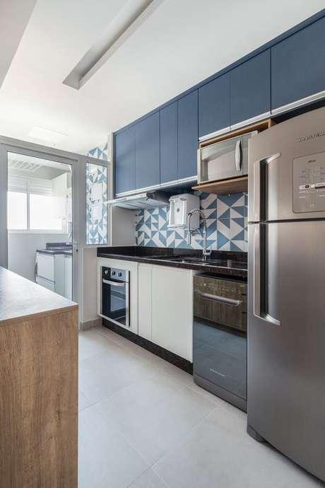 39. Cozinha com armário azul e revestimento geométrico – Via: Rubiam Vieira Interiores