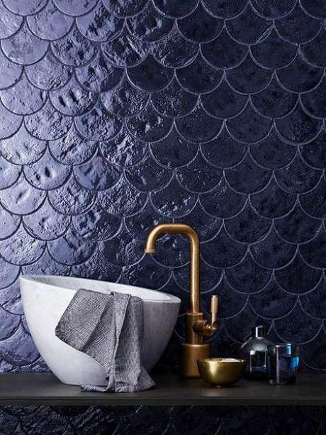 50. Banheiro em revestimento azul marinho com torneira dourado – Via: Micasa Revista