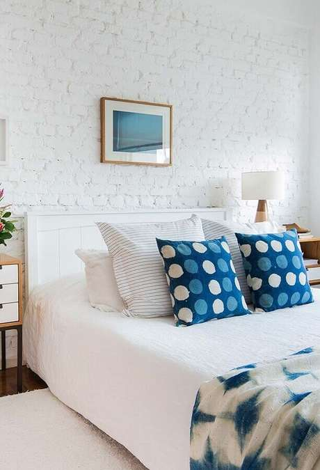 8. Cores claras para quarto de casal com parede de tijolinho branca e almofadas azuis – Foto: Sua Decoração