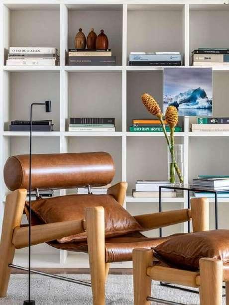 19. Poltrona de couro moderna para decoração de ambiente com estante de nichos – Foto: Casa de Valentina