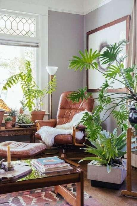 20. Decoração simples com poltrona de couro para sala com vasos de plantas – Foto: Archidea