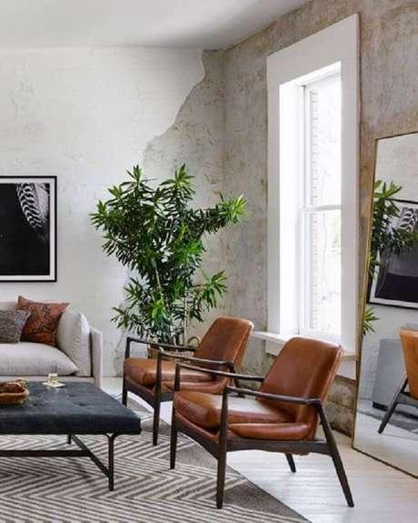 21. Sala rústica decorada com poltrona de couro e madeira – Foto: Horchow