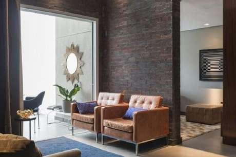 25. Decoração de sala com parede rústica e poltrona de couro marrom – Foto: Mauricio Karam