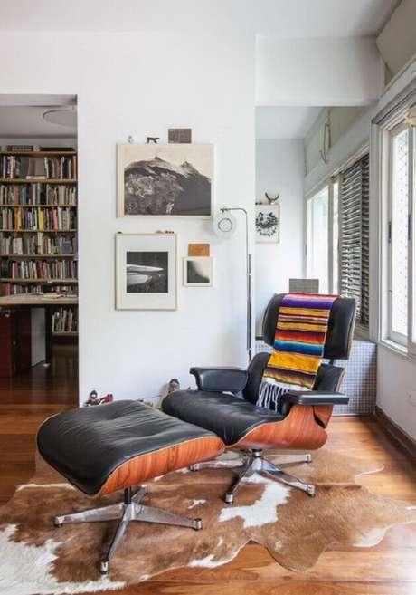 30. Manta colorida para decoração de poltrona de couro preta confortável – Foto: Histórias de Casa