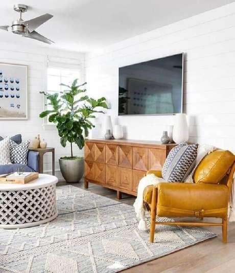 35. Decoração para sala de TV com sofá azul, tapete cinza claro e poltrona de couro caramelo – Foto: Pinterest
