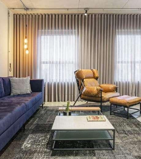 37. Poltrona de couro caramelo para sala moderna decorada com tapete cinza e sofá azul – Foto: Jeito de Casa