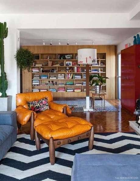 7. Poltrona de couro caramelo para sala decorada com tapete preto e branco e estante de madeira – Foto: Histórias de Casa