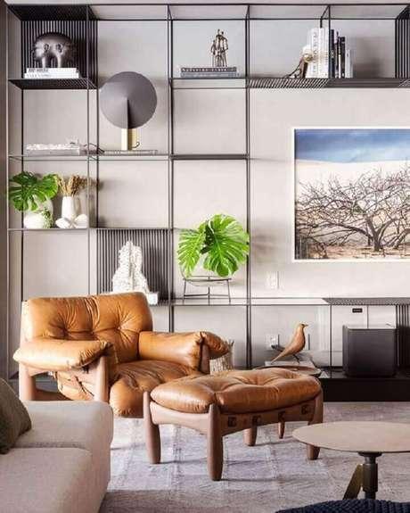 40. Sala moderna decorada com poltrona de couro caramelo e estante industrial – Foto: Pinterest