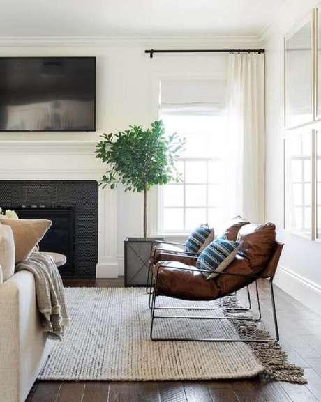 43. Decoração em cores claras para sala com lareira e poltrona de couro moderna – Foto: McGee & Co.
