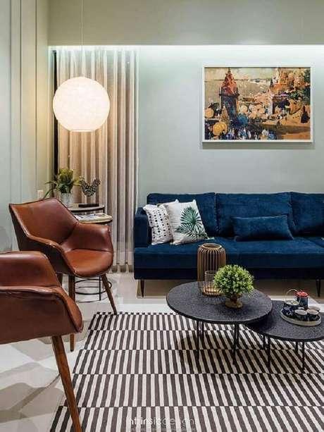 45. Poltrona de couro marrom para sala de estar decorada com sofá azul escuro e tapete listrado – Foto: Horchow