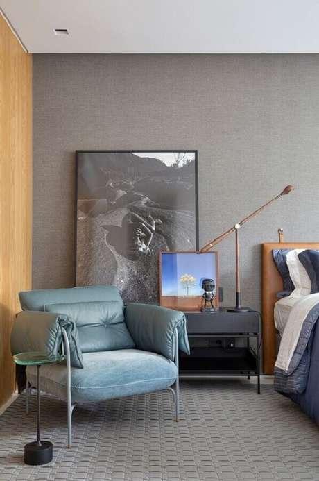 48. Poltrona de couro cinza para quarto moderno decorado com quadro grande e cabeceira de couro marrom – Foto: Casa de Valentina