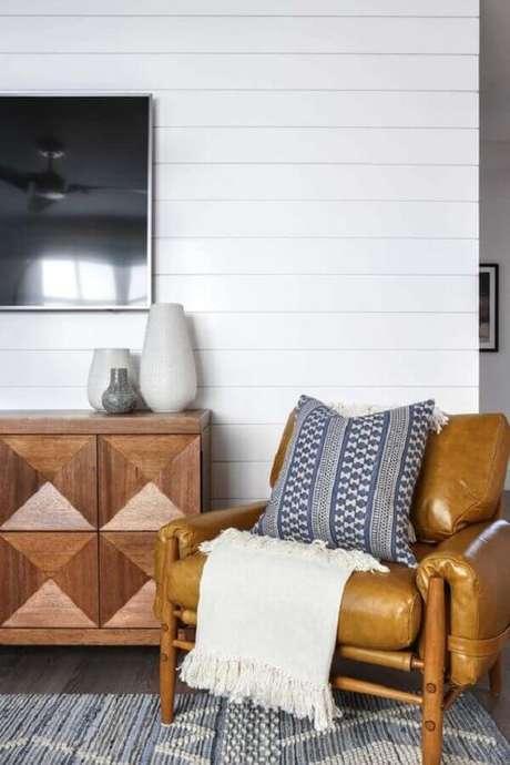 49. Poltrona de couro e madeira para sala de TV decorada com manta bege – Foto: One Kindesign