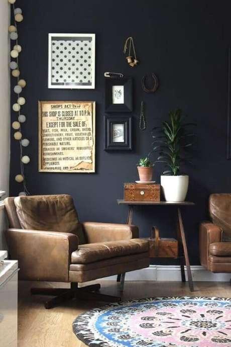 52. Sala decorada com parede preta e poltrona de couro giratória – Foto: Pinterest