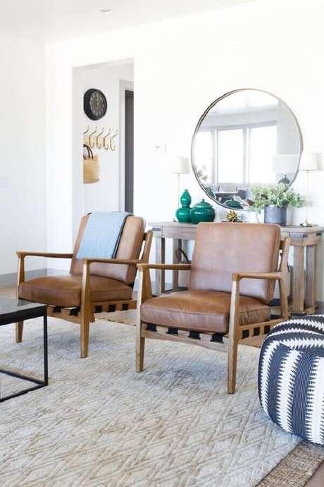 53. Espelho redondo para sala branca decorada com poltrona de couro e madeira – Foto: Style Me Pretty