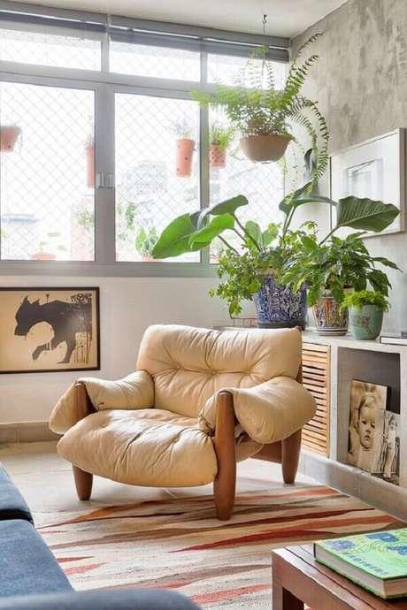 54. Poltrona de couro bege confortável para sala de estar com tapete colorido – Foto: Casa de Valentina