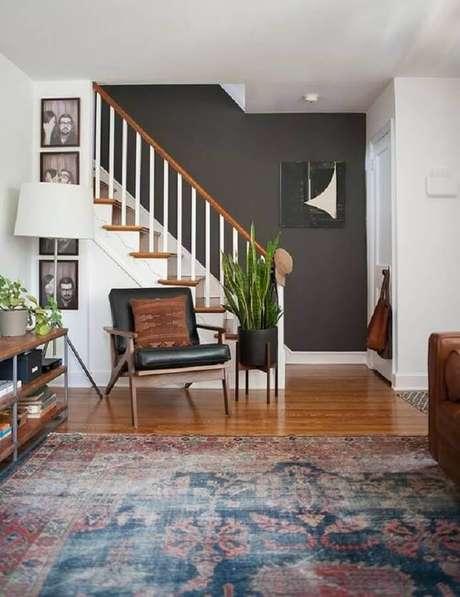 56. Poltrona de couro preta para sala de estar decorada com abajur de chão – Foto: domino magazine
