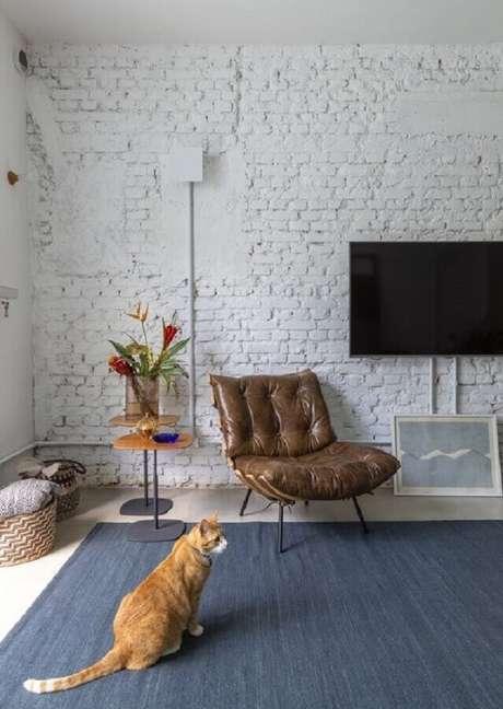 58. Poltrona de couro marrom escuro para sala de TV rústica decorada com parede de tijolinho branca – Foto: INÁ Arquitetura