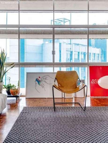 59. Sala decorada com tapete geométrico e poltrona de couro moderna – Foto: Histórias de Casa